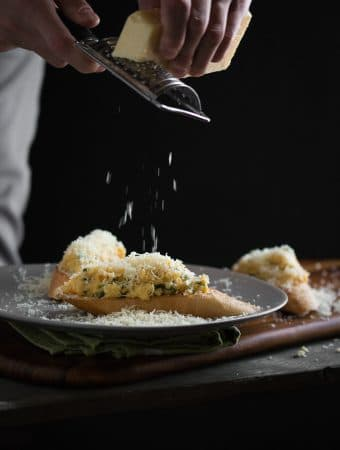A dark, moody photo of Parmesan cheese being grated on top of cheesy scrambled eggs on toasted bread.