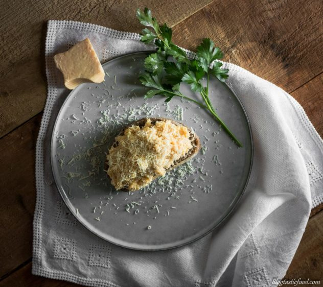 An overhead photo of scrambled eggs on toast, finished with Parmesan cheese.