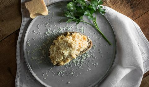 A plate the scrambled eggs on toast with Parmesan cheese on it, with a sprig of parsley and a block of Parmesan cheese beside it.