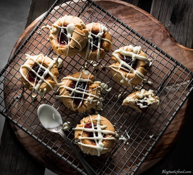An overhead photo of peanut butter and jam cookies that have just been drizzled with white chocolate.