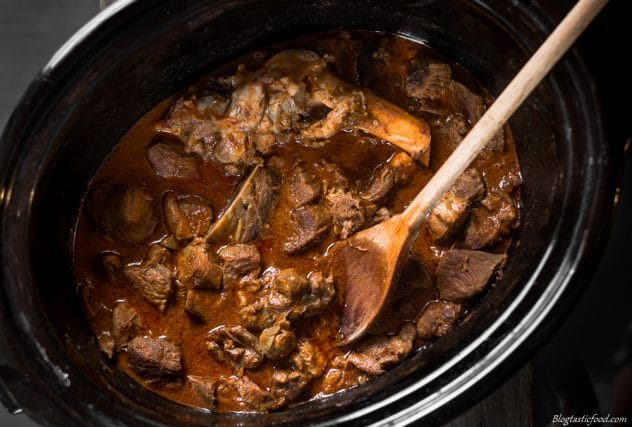 An overhead photo of lamb rogan josh in a slow cooker.