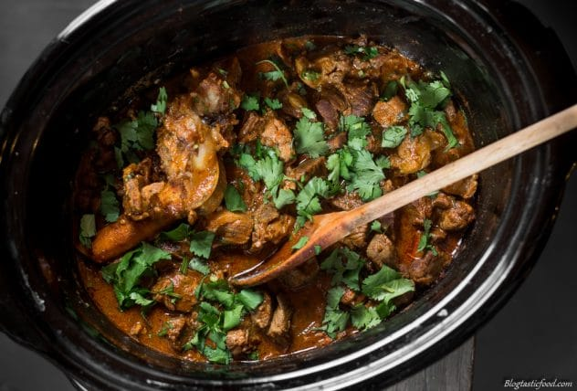 An overhead photo of lamb curry in a slow cooker garnished with coriander.