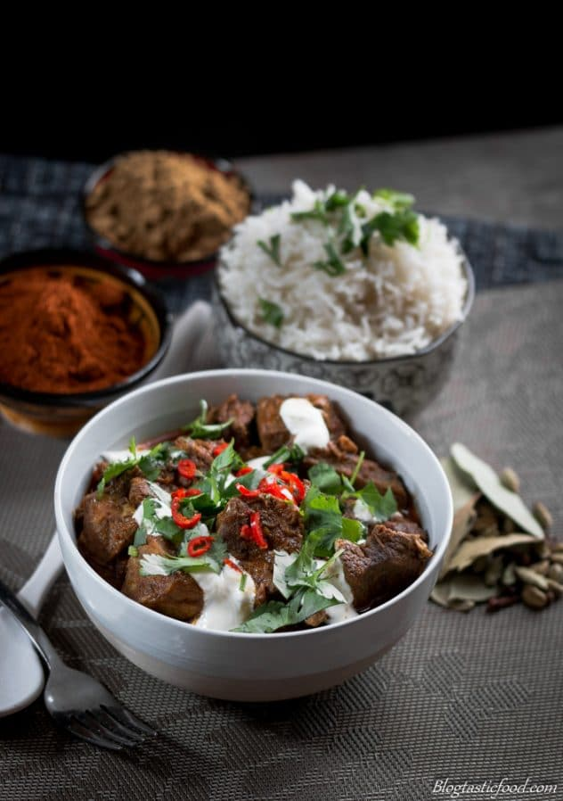A bowl of Lamb Rogan Josh garnished with yogurt, coriander and fresh chili.