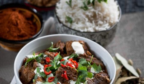 A bowl of Lamb curry with rice and spices in the background.
