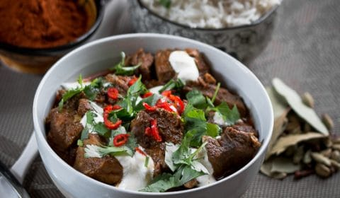 A contrast photo of Lamb Rogan Josh garnish with yogurt, coriander and fresh chili.