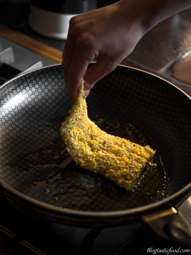 A raw piece of polenta coated fish being added to a non-stick pan to fry.