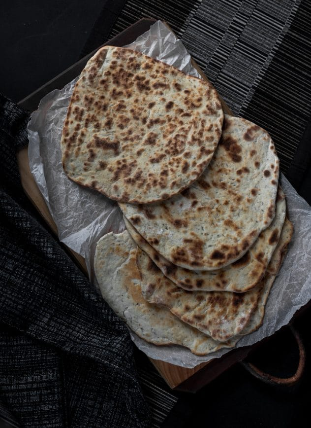 A photo of flat breads served on top of a chopping board and scrunched up baking paper.