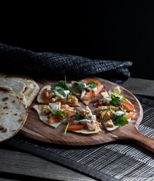 Flatbread with chicken, tomato, sour cream and parsley on top served on a circle board.