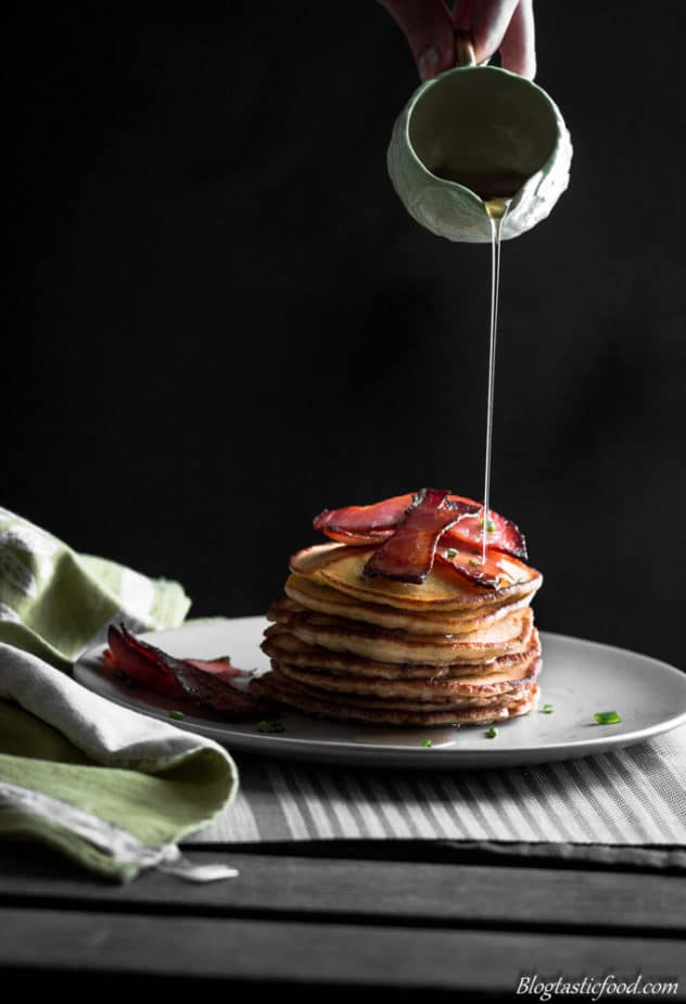 A stack of thick, fluffy pancakes with crispy bacon and maple syrup being poured over the top.