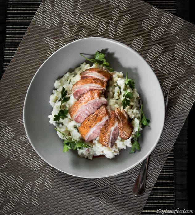 An overheat photo of herb risotto with sliced of duck breast on top.