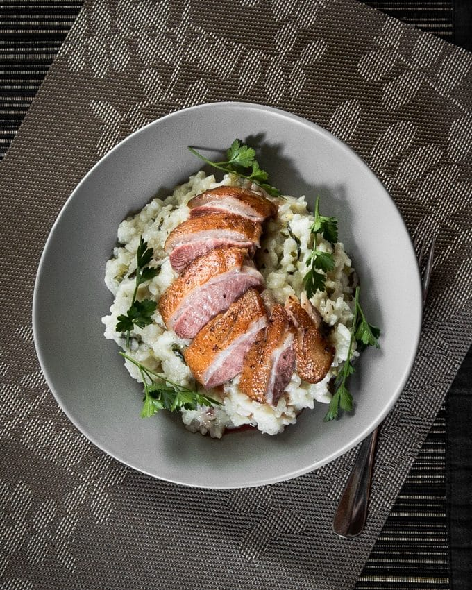 Slices of medium rare pan seared duck breast on herb risotto.