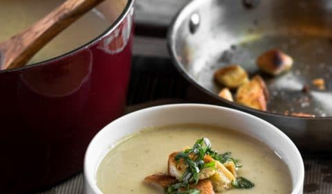 Roasted cauliflower and leek soup served in a bowl that has been garnished with croutons and basil.