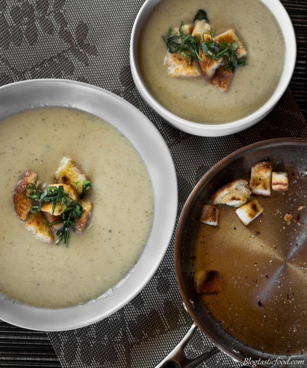 A overhead photo of cauliflower and leek soup in 2 bowls with a pan of croutons.
