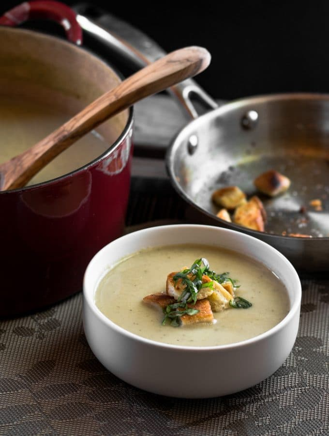 A photo of a cauliflower and leek soup with croutons.