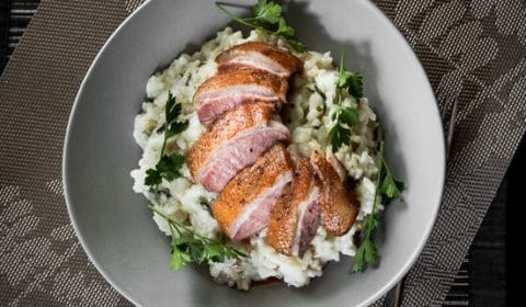 Risotto with pan seared duck breast on top garnished with parsley.