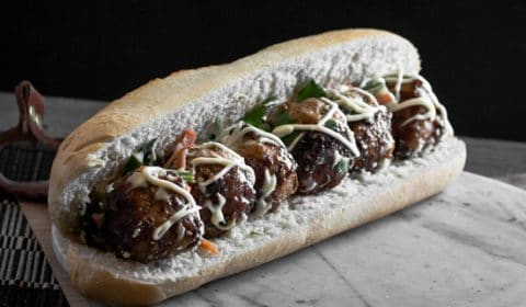 A photo of Asian meatballs, Japanee mayo an pickled veg in a white bread roll.
