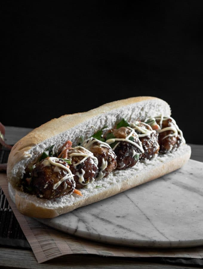 A photo of an Asian meatball sub in a marble surface.