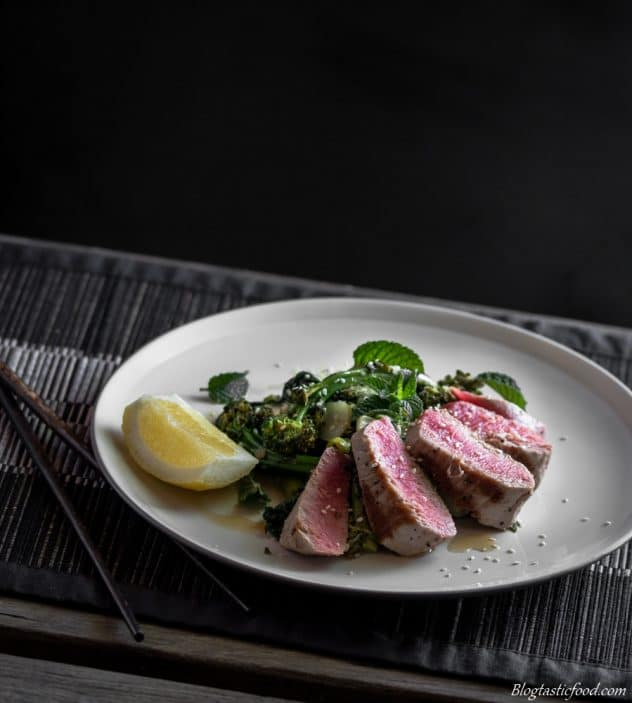 Mixed greens, a lemon wedge and seared tuna served on a plate.