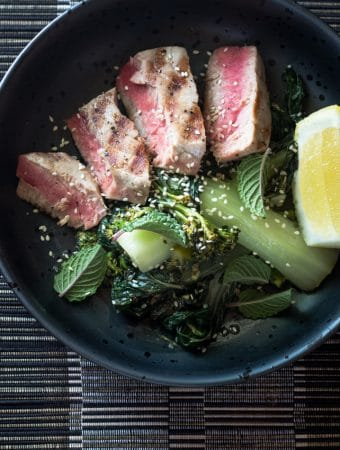 An overhead photo of seared tune and mixed greens.