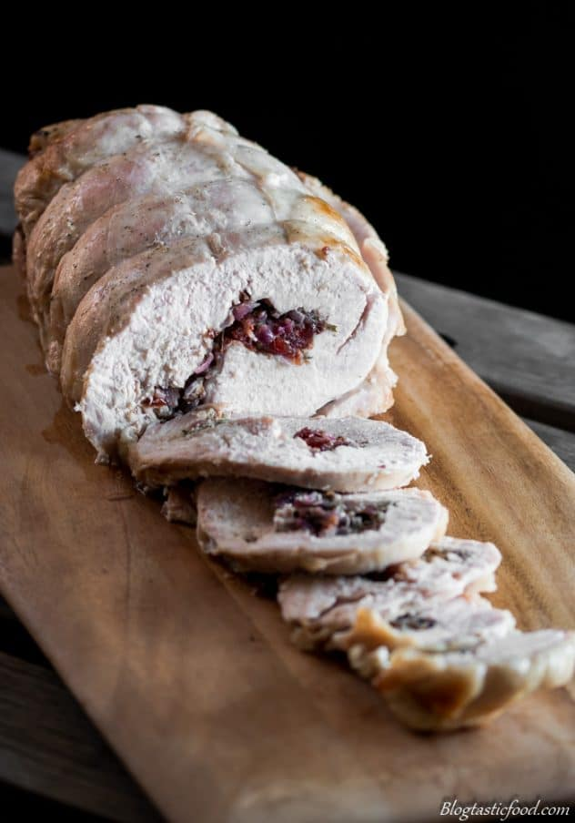 A cooked brined turkey with with cranberry stuffing served on a chopping board.