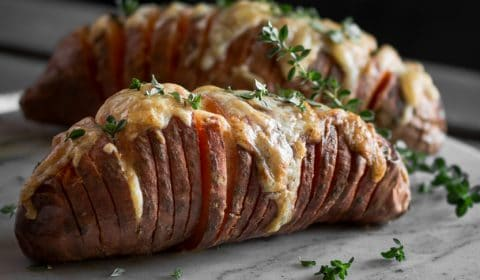 A hasselback sweet potato that has been garnished with fresh thyme.