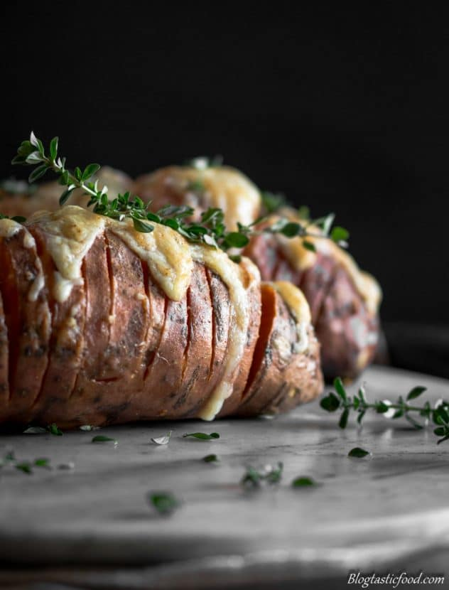 An eye level photo of a hasselback sweet potato with melted cheese on top.
