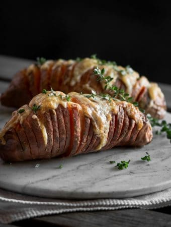 A photo of cheesy Hasselback sweet potatoes on a marble surface.
