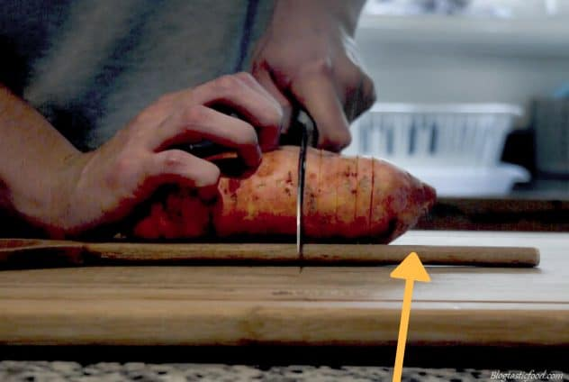 A photo demonstrating you to cut a sweet potato to make a hasselback sweet potato.