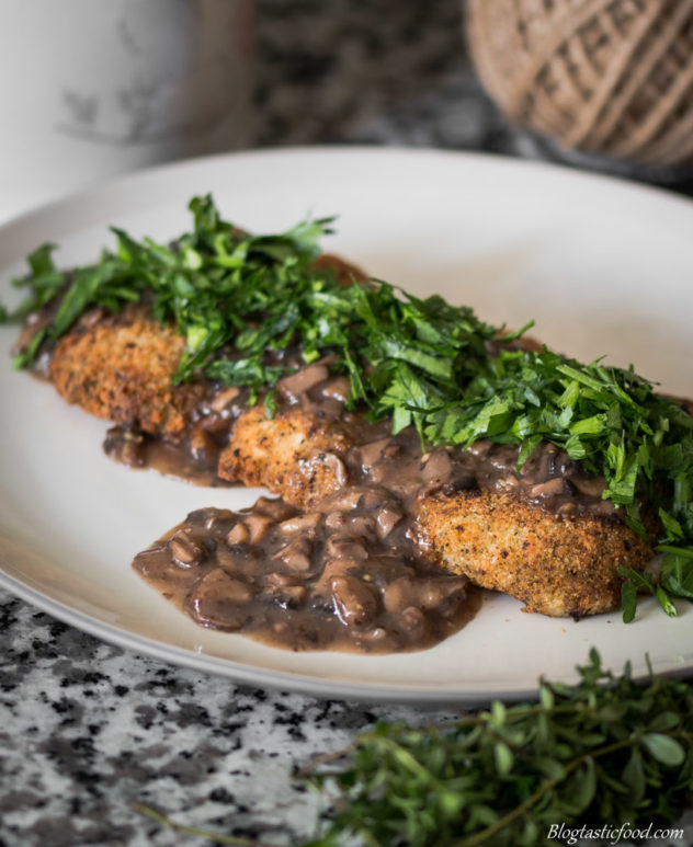 3 fish fillets, topped with mushroom gravy, garnished with chopped parsley.