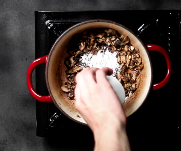 A photo of someone adding flout to a pot filled with sauteing mushrooms.