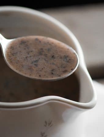 A close up photo of mushroom gravy in a spoon.