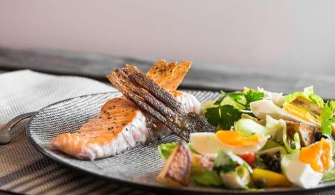 A photo of nicoise salad with crispy skin salmon.