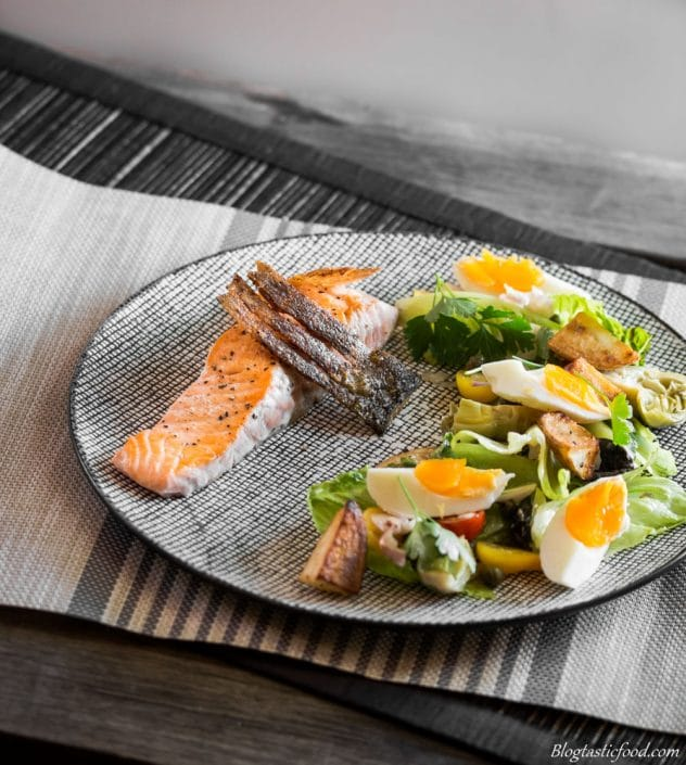 Salmon with crispy skin served on a plate with a nicoise salad.