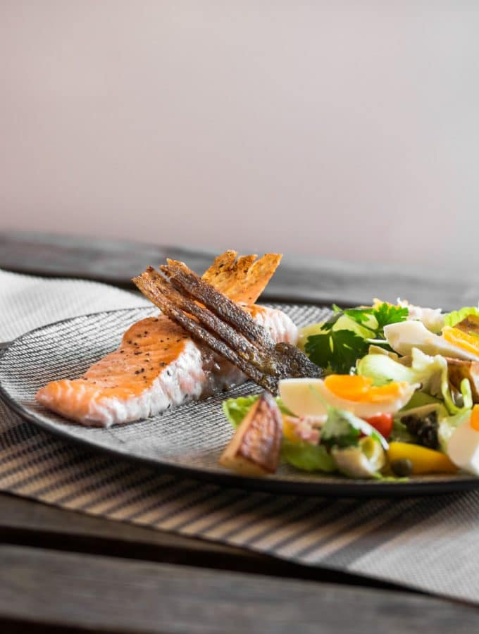 A nicoise salad served with a pan seared fillet of salmon.