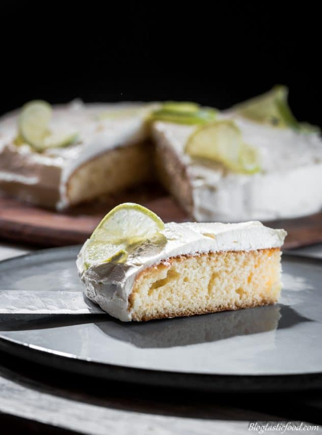 A picture of rosewater cake coated in citrus buttercream garnished with a thin slice of lime.