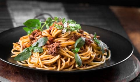 A dark contrast photo of spaghetti with shredded beef bolognase that has been served neatly on a plate and garnished with basil.
