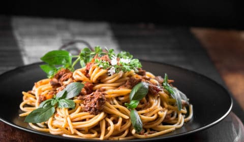 A photo of shredded beef spaghetti bolognese on a black plate.
