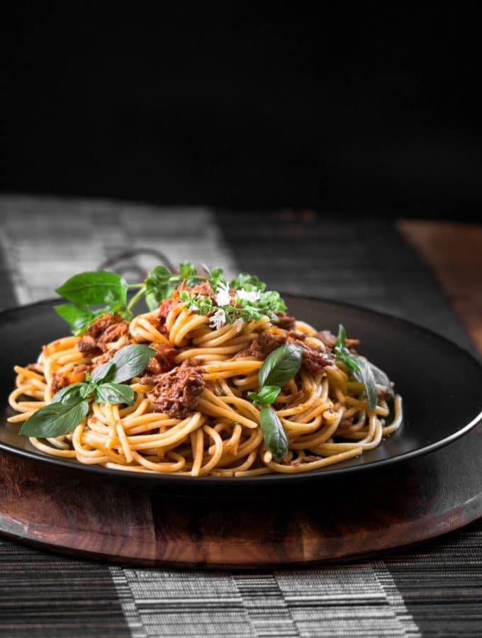 A dark contrast photo of spaghetti with shredded beef.