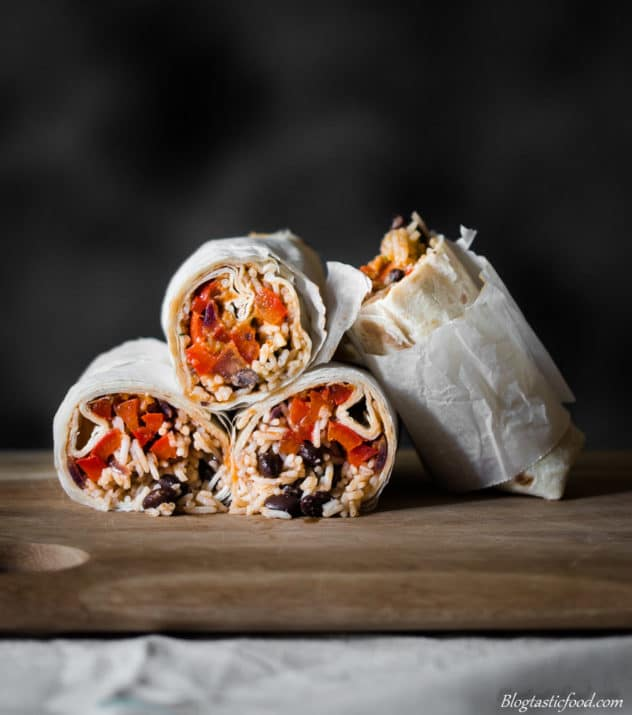 A eye level photo of burritos cut in half, exposing the filling.
