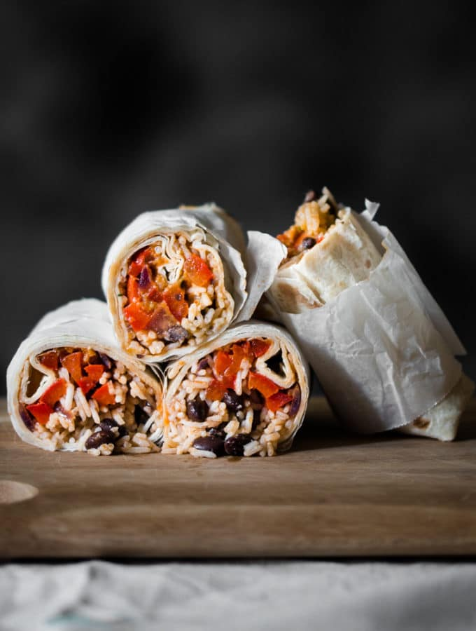 A photo of 2 vegan burritos that are cut in half and served in a wooden board.