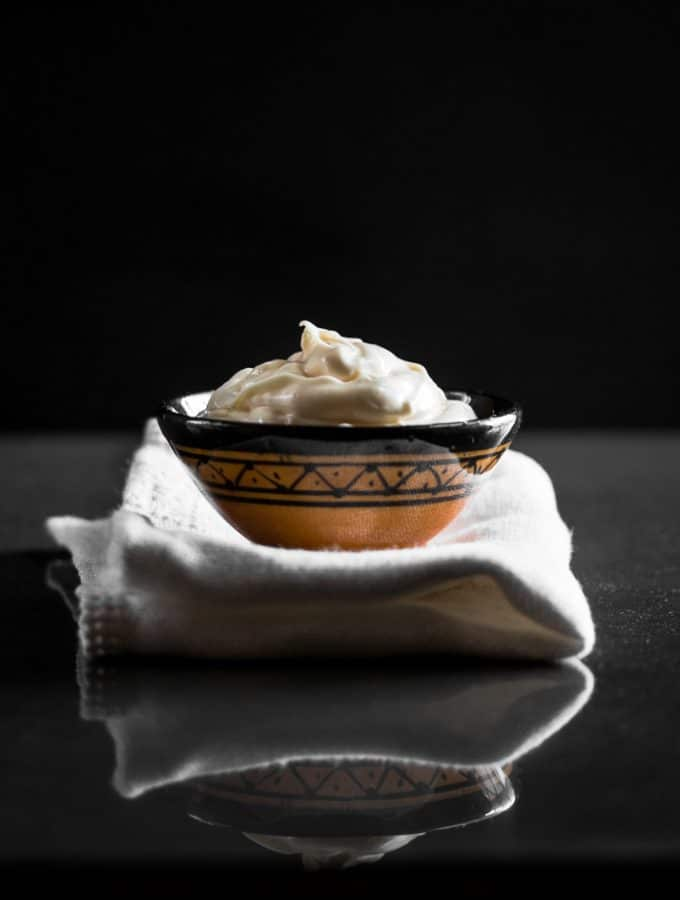 A contrast eye level photo of aioli served in a small bowl on a white cloth.