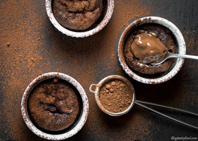 An overhead shot of 3 chocolate lava cakes dusted with cocoa powder.