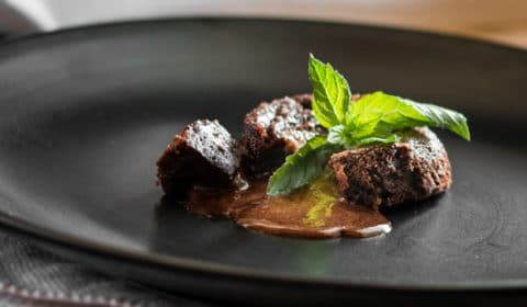 Chocolate lava cake served on a black plate.