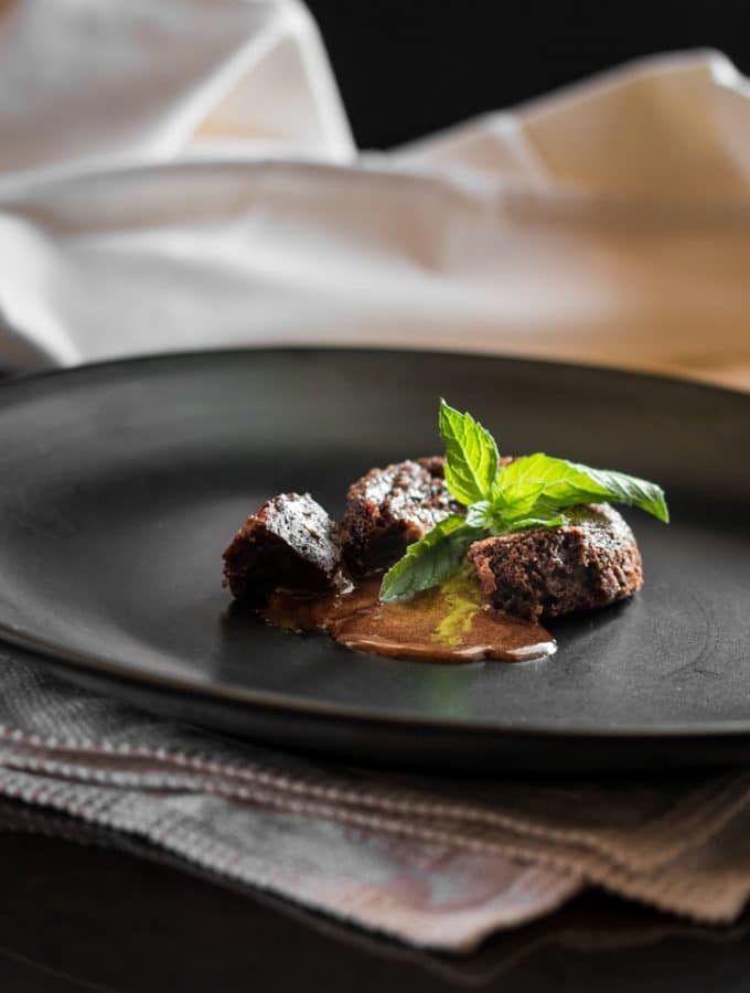 A photo of chocolate lava cake garnished with a sprig of mint.