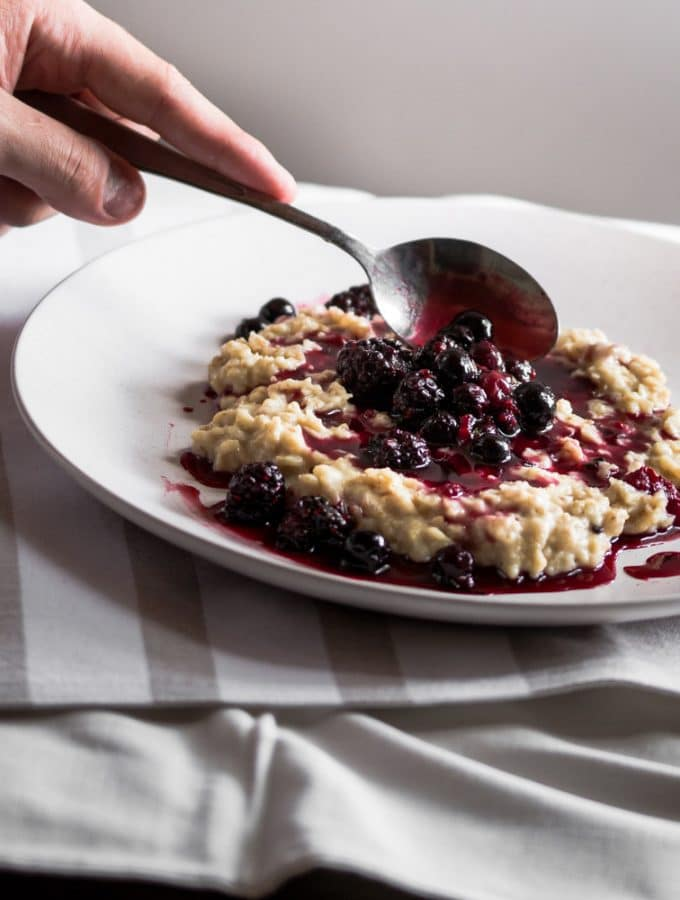 Porridge on a white plate with stewed berries being spooned over the top.