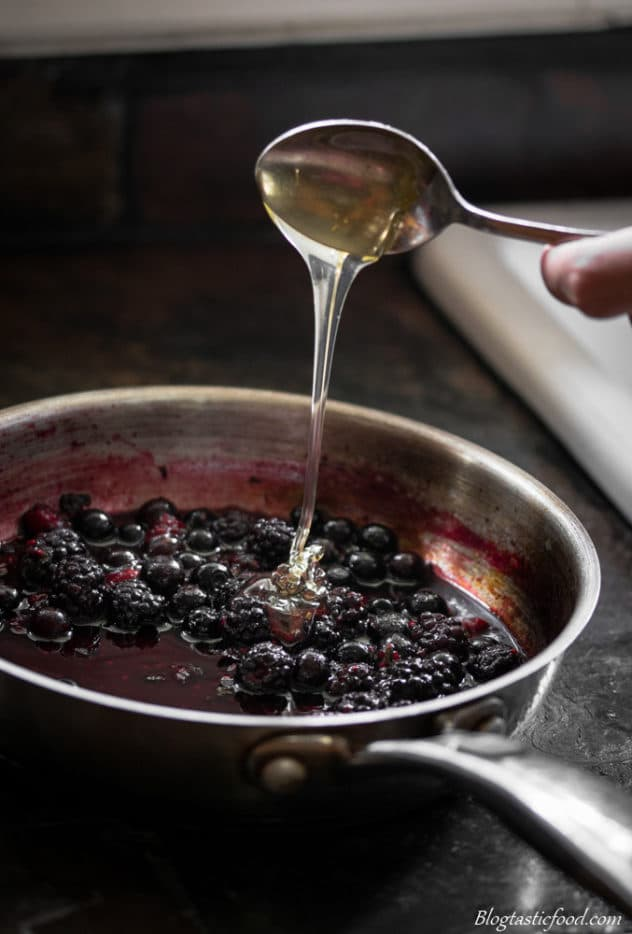 Honey being drizzled into a pan of stewed berries.