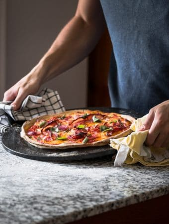 A pizza Margherita with crispy prosciutto on a black pizza slate.