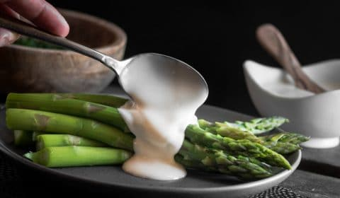 A photo of asparagus and hollandaise sauce on a dark plate.