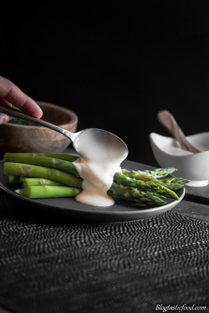 A photo of asparagus and hollandaise sauce on a dark plate.