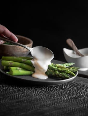 Hollandaise sauce being spooned over a plate of blanched asparagus.